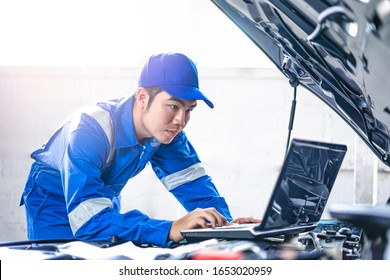 Close up concept of male asian car mechanic using a computer laptop to diagnosing and checking up on car engines parts for fixing and repair, working on the car engine wearing blue overall and a hat