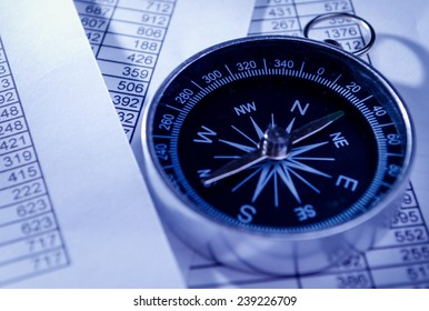 Close up Conceptual Compass Instrument on Top of Paper Reports with Numerical Prints in a Table.