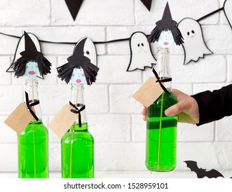 Close up of conceptual and creative green Halloween drinks with witches heads over white bricks wall background