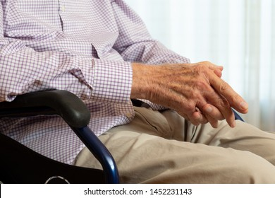 Close up conceptual detail shot of old disabled man in wheelchair. Senior sitting with hands together on lap in living room.