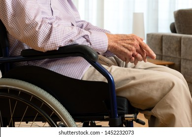 Close up conceptual detail shot of old man sitting in wheelchair with hands on lap indoors.