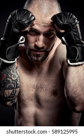 Close up Conceptual Portrait of brutal tattooed boxer in boxing gloves on grey background. Art Sport background.