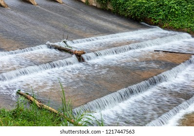 Close up of concrete weir with water flowing down at rural village in Thailand