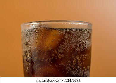 Close up of condensed glass full with cola soda drink with ice cube in orange background, hot and thirsty concept