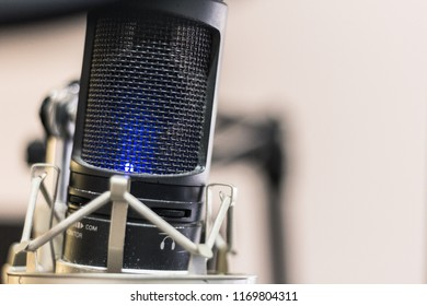 Close up Condenser microphone on holder with blue light swith on and copy space on white background