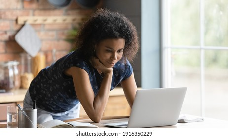 Close up confident African American woman using laptop, standing at table in kitchen, working on research project or studying online at home, watching webinar on computer screen, reading news