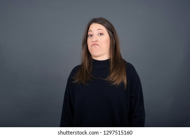 Close up confident brunette businesswoman showing skeptical facial expression while looking at the camera. Isolated on gray background.