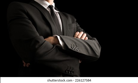 Close up Confident Businessman in Black Elegant Business Suit with Crossed Arms in Front of the Body. Isolated on Black Background.
