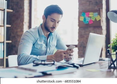 Close up of confident handsome young middle eastern lawyer guy is browsing information on his smart phone at work place