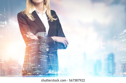 Close up of a confident businesswoman�s torso with crossed arms standing against a city panorama. Mock up. Toned image. Double exposure