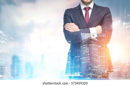 Close up of a confident businessman�s torso with crossed arms standing against a city panorama. Mock up. Toned image. Double exposure