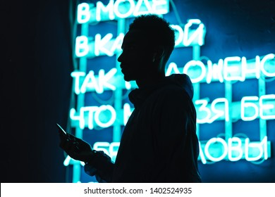 Close up of a confident young african man silhouette wearing windbreaker using mobile phone while standing outdoors close to a neon signboard