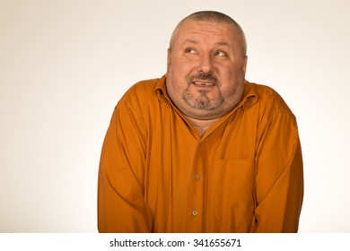 Close up of confused and doubtful man with big head in orange shirt
