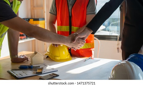 Close up construction worker or engineer shaking hands after finish an agreement or contract.