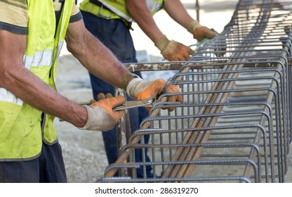 Close up of construction worker hands working with pincers on fixing steel rebar at building site