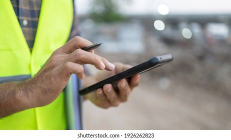 Close up construction worker holding a pen using smartphone construction site