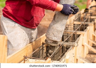 Close up of construction worker laying cement or concrete into the foundation formwork with automatic pump. Building house foundation