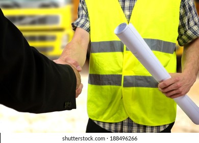 Close up of a construction worker's hand holding project documents and shaking hands.