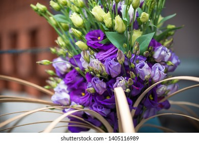 close up of a contemporary bouquet with various purple lisianthus flowers on a blue barn door