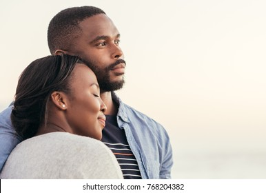 Close up of content young African couple enjoying a late afternoon together on a sandy beach at sunset while standing in each other's arms