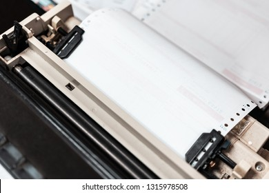 Close up of continuous paper being feed into old dot matrix printer. Dot matrix printer can print multiple (copy) of document or receipt at once.