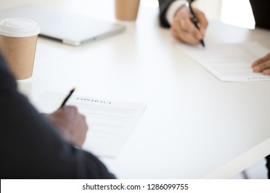 Close up contract paper official document, signed by diverse international partners sitting at desk during business meeting. Make a deal, good result, commitment and pecuniary liability concept