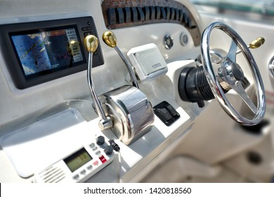 Close up at control panel navigation instruments with chromed wheel on fishing and leisure boat