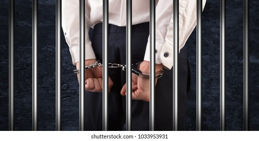 Close convicted man with handcuffs behind grids