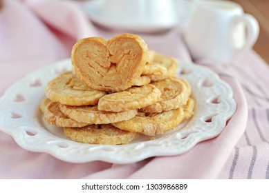 Close up of cookies palmier - Sweet puff pastry in shape of heart on the pink tablecloth.Concept about love and relationship.Valentine idea with copy space.