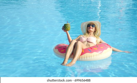 CLOSE UP COPY SPACE Happy young woman on summer vacation lying on inflatable doughnut floatie in pool, drinking pineapple alcohol beverage. Smiling girl floating on inflatable pillow & sipping drink