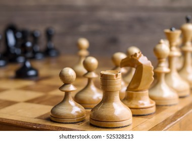 Close up corner view of chess pieces lined up on a chess board ready for a game with selective focus to a white castle