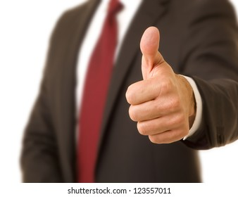 Close up of a corporate executive wearing a suit and tie giving the thumbs up sign selective focus