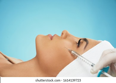 Close up of cosmetic botox injection in female cheek. Cosmetologist using syringe with filler while young pretty patient in towel on head lying, isolated on blue. Concept of cosmetology, beauty.