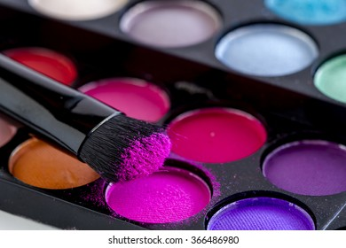 Close up of cosmetic brush with hot pink eye shadow dust sitting on top of colorful palette of eye shadows