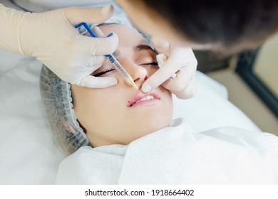 Close up of cosmetic injection in female lips. top view of cosmetologist using syringe with special liquid and holding patients chin, Concept of cosmetology, beauty.