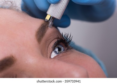 Close up of a cosmetologist applying a special permanent make up on a  woman's eyebrows.