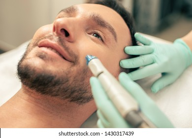 Close up of the cosmetologist conducting the skin nourishing procedure on the face of bearded man