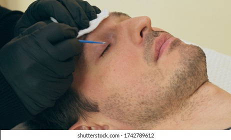 Close up of cosmetologist preparing man for the eyelash extension procedure. High quality close-up of a man laying on a couch during the esthetician lash treatment. Cosmetology service.