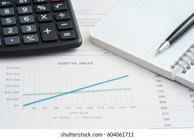 Close up of cost vs sales, with financial graphs