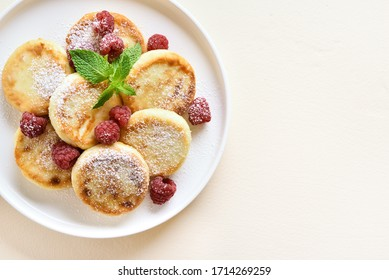 Close up of cottage cheese pancakes with fresh raspberries on plate over light stone background with free text space. Top view, flat lay