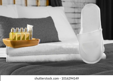 Close Up Cotton Hotel towel with shampoo, papper slippers and soap bottle set on white bed with bamboo board.  White Brick wall and grey blanket on background.