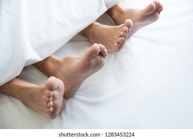 Close up of couple barefoot under blanket in bedroom in honeymoon vacation holiday in long weekend at home. Relaxation of sexual and romantic people after wedding ceremony. Valentines day love theme.