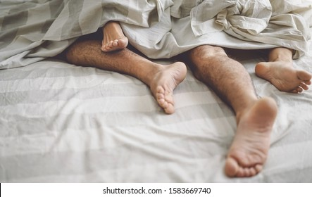 Close up couple feet in bed - Young lovers intimate and passionate moments under white sheets in bedroom - Love relationship and intimacy people concept
