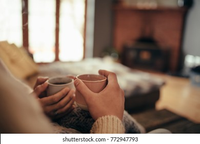 Close up of couple hands holding coffee while sitting on sofa at home, focus on hands and coffee.
