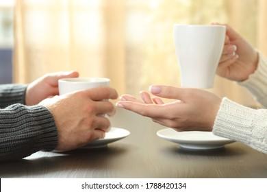 Cierre de un par de manos hablando con tazas de café sentadas en una mesa al lado de la ventana en casa