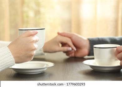 Cierre de una pareja tomándose de la mano con tazas de café sentadas en una mesa al lado de la ventana en casa