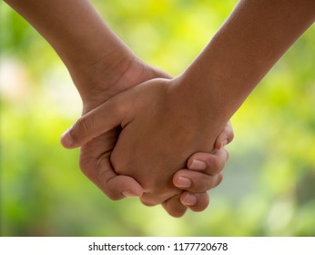 close up of couple holding hands on blurred background