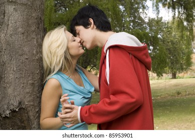 Close up Couple kissing next to tree in garden or park
