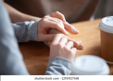 Close up couple in love sitting in cafe together, holding hands, young girlfriend and boyfriend on first date, good relations, trusted friends meeting in public place together, true friendship