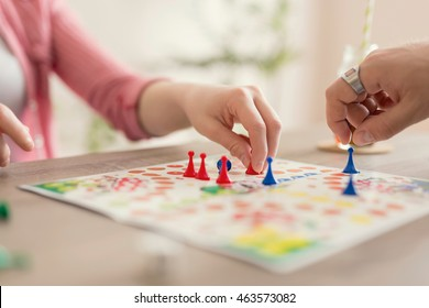 Close up of a couple in love sitting on the floor next to a table, playing ludo board game and enjoying their free time together. Focus on the red figurine